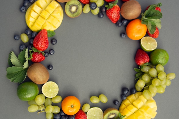 Fruits d'été, cadre. raisins, mangue, fraise, myrtille, kiwi, menthe, citron vert.