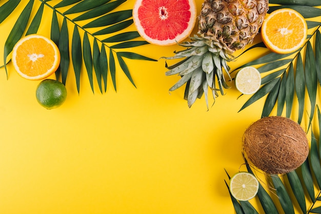 Fruits d'été. feuilles de palmier tropical, ananas, noix de coco, pamplemousse, orange et citron vert sur fond jaune.