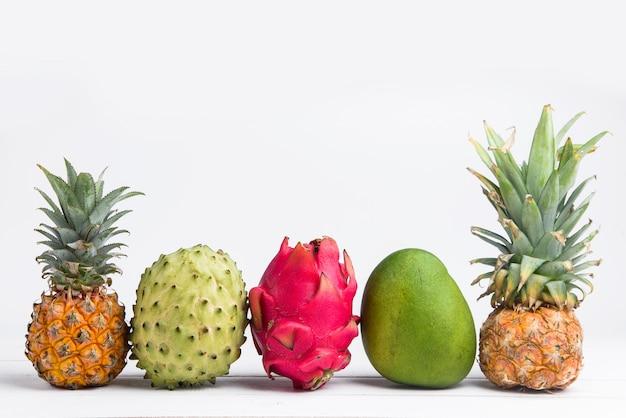 Fruits d'été frais exotiques sur blanc. fruit du dragon, ananas, kaki, mangue, annona cherimola à plat avec espace de copie gratuit.