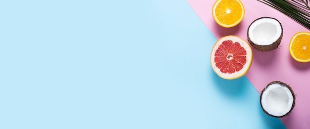 Fruits exotiques sur fond rose bleu. noix de coco, orange, pamplemousse.
