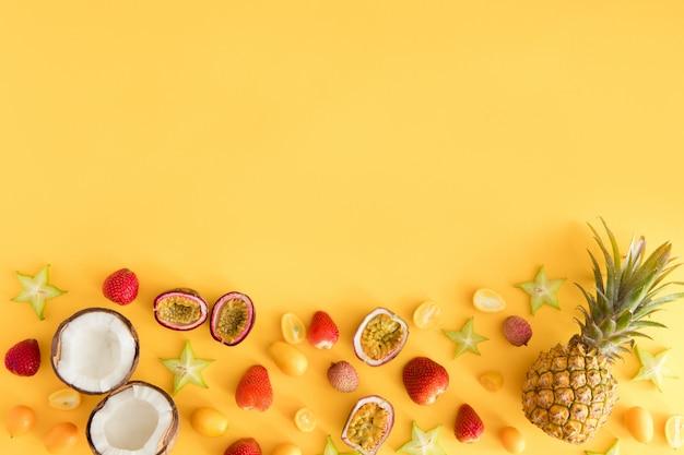 Fruits exotiques frais colorés sur une table jaune pastel.