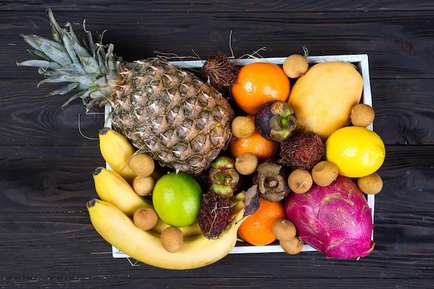 Fruits exotiques frais dans une boîte en bois, vue de dessus avec de nombreux fruits mûrs colorés