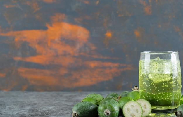Fruits feijoa et verre de jus sur table en marbre.