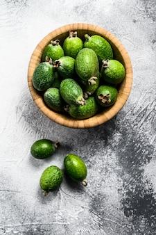 Fruits feijoa verts dans une assiette en bois sur un fond gris. feijoa aux fruits tropicaux. vue de dessus