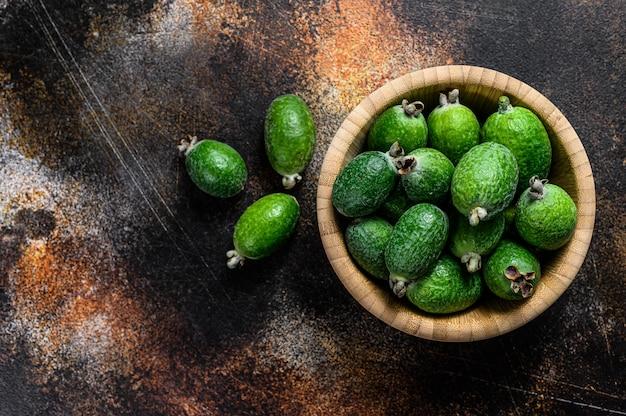Fruits feijoa verts dans une assiette en bois sur un fond sombre. feijoa aux fruits tropicaux. vue de dessus
