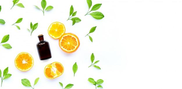 Fruits et feuilles d'orange fraîche avec une bouteille d'huile essentielle sur un mur blanc.