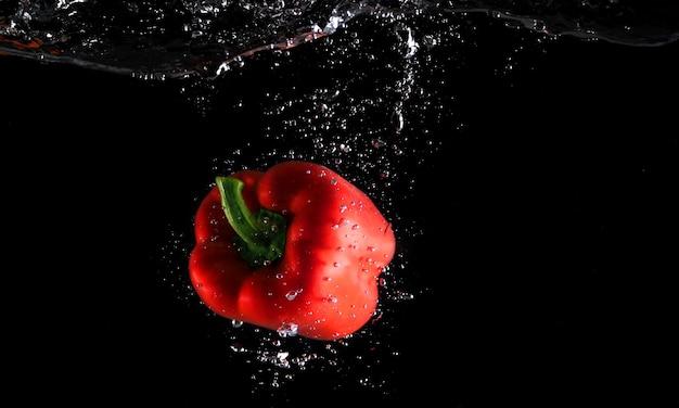 Fruits de fraîcheur colorés tombant dans les éclaboussures d'eau et fond noir