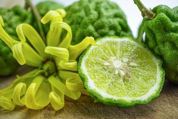 Fruits frais bergamote sur fond en bois avec fleur jaune.