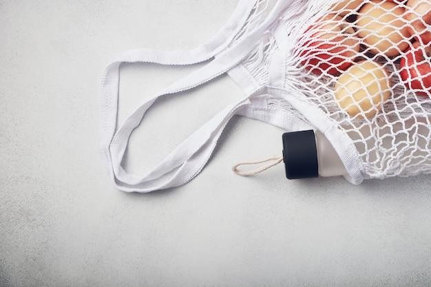 Fruits frais et bouteille d'eau dans un sac en filet écologique blanc. concept zéro déchet