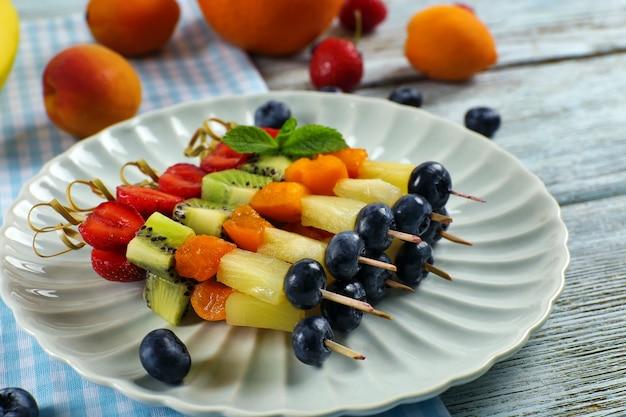 Fruits frais sur des brochettes en assiette sur table, gros plan