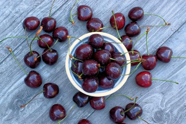 Fruits frais de cerise dans un bol sur un fond en bois.