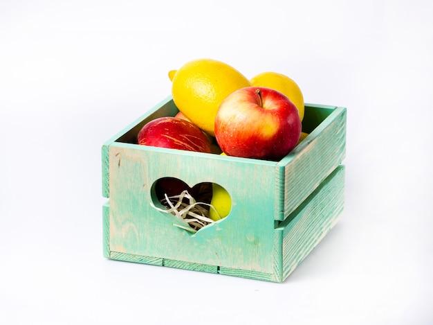 Fruits frais dans une boîte en bois isolé sur blanc