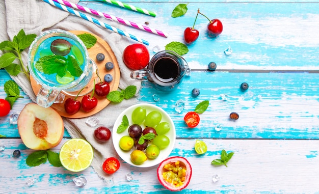 Fruits frais d'été. pomme. cerise. citron vert. grain de raisin. sur une table en bois blanche bleue.