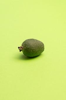 Fruits frais de feijoa sur une surface vert vif.