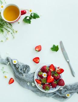 Fruits frais fraise, fleurs, feuilles sur table en bois blanc