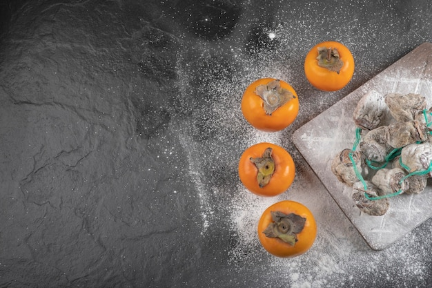 Fruits frais de fuyu et de kaki séchés sur la surface noire