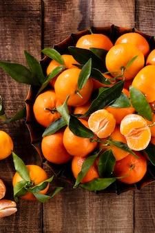 Fruits frais de mandarines ou de mandarines avec des feuilles dans une boîte en bois, vue de dessus