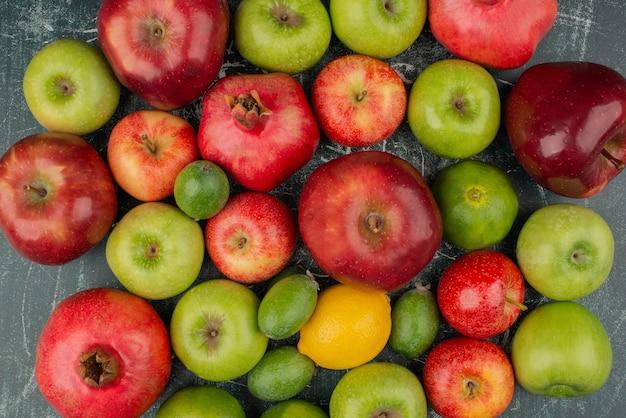 Fruits frais mélangés éparpillés sur une surface en marbre.