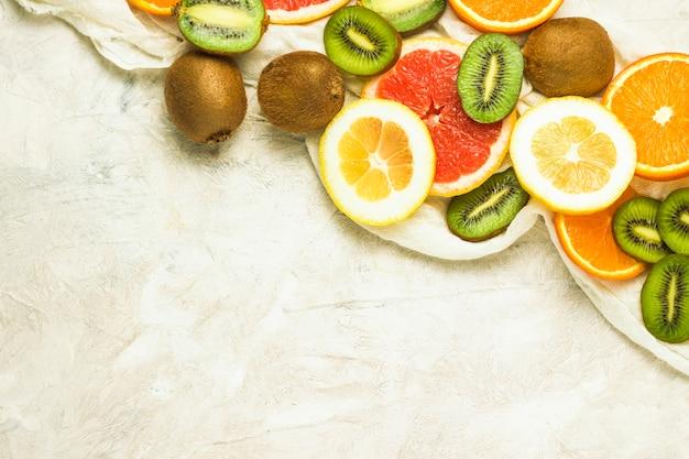 Fruits frais, pamplemousse, citron, orange, kiwi sur fond de pierre claire. espace copie et vue de dessus