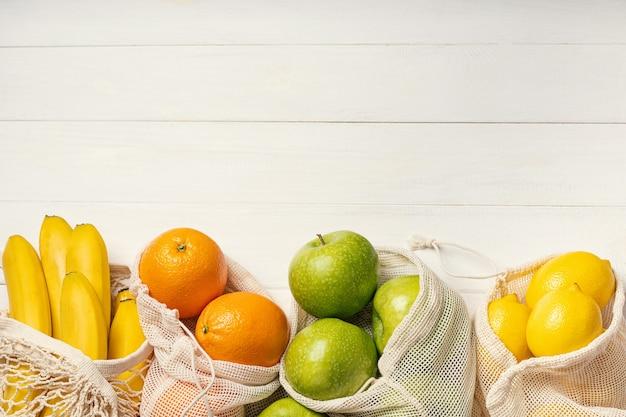 Fruits frais, pommes, bananes, oranges et citrons en bordure de sacs écologiques
