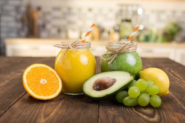 Fruits frais et pot avec smoothie sur table de cuisine