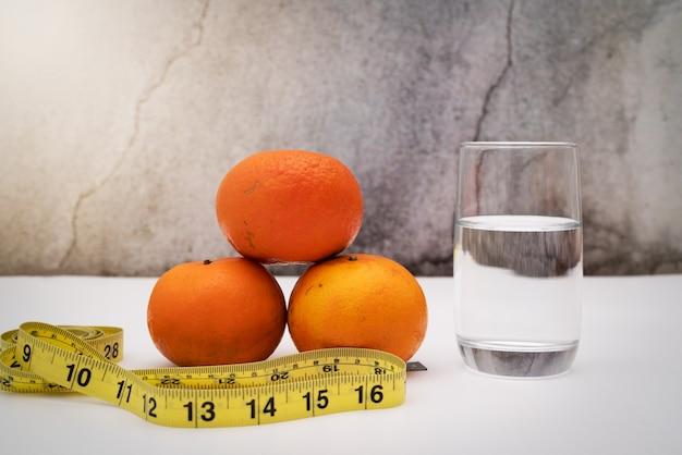 Fruits frais pour régime alimentaire, ruban à mesurer et eau potable sur fond grunge. concept de régime et de mode de vie sain
