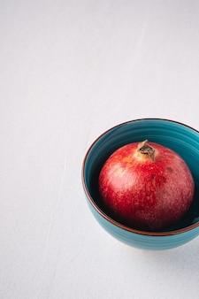 Fruits de grenade dans un bol bleu sur blanc