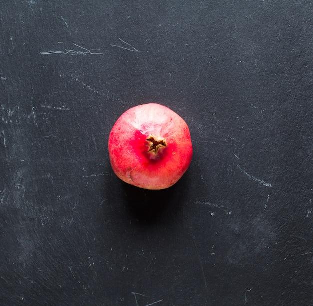 Fruits de grenade sur fond de bois rustique, espace libre avant le texte.