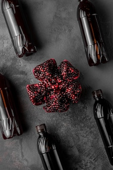 Fruits de grenade tranchés et de nombreuses bouteilles avec boisson exotique sur fond sombre, vue de dessus