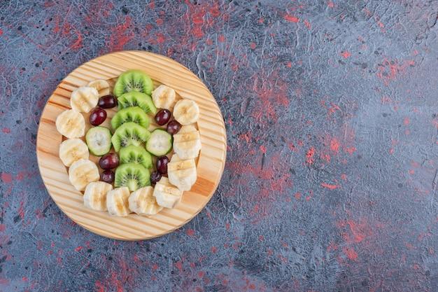 Fruits hachés et tranchés dans une assiette en bois.
