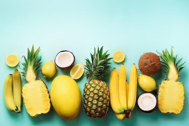 Fruits jaunes biologiques frais sur fond bleu. concept monochrome avec banane, noix de coco, ananas, citron, melon.