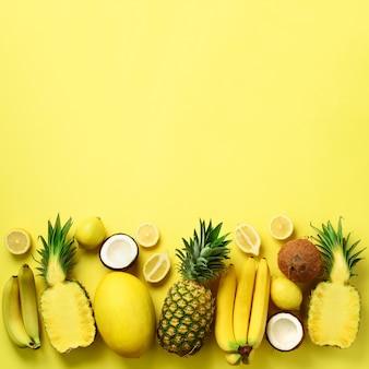 Fruits jaunes biologiques frais sur fond ensoleillé. concept monochrome avec banane, noix de coco, ananas, citron, melon.