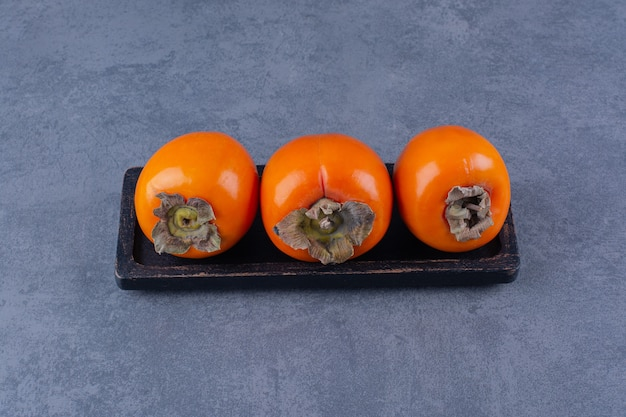 Fruits de kaki frais et biologiques à bord sur une table en marbre.