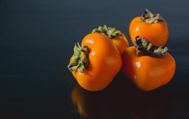 Fruits de kaki frais délicieux sur fond noir.
