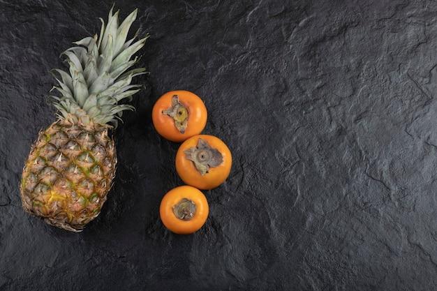 Fruits de kaki savoureux et ananas mûrs sur une surface noire