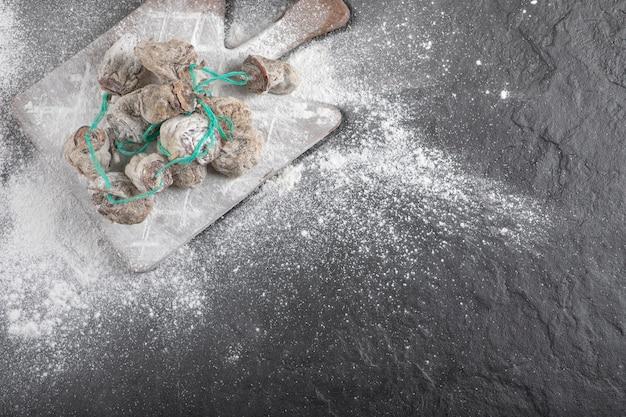Fruits de kaki séchés décorés de farine sur une surface noire