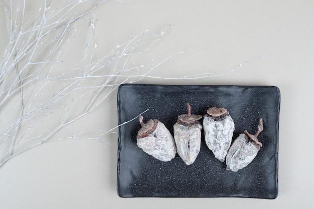 Fruits de kaki séchés sur plaque noire