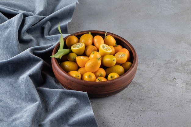 Fruits kumquat dans un bol sur un morceau de tissu, sur la surface en marbre