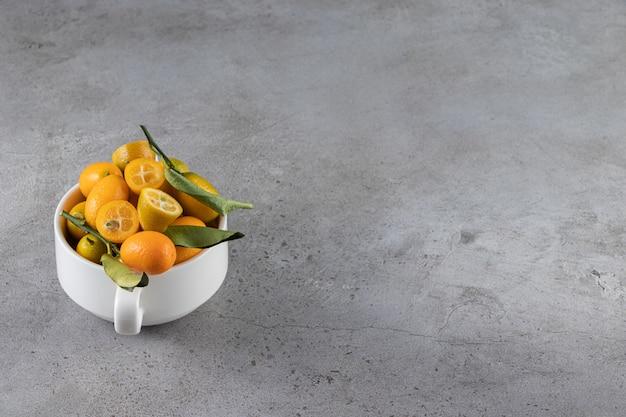 Fruits de kumquat dans une tasse, sur la surface en marbre