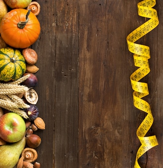 Fruits, légumes et céréales d'automne avec ruban à mesurer sur la table en bois vue de dessus avec copie espace