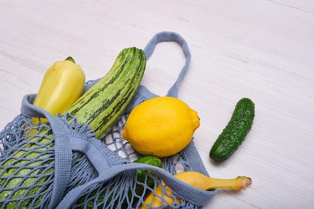 Fruits et légumes dans un sac en filet sur un fond en bois