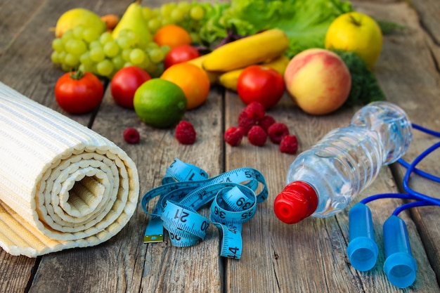 Fruits, légumes, eau, ruban à mesurer et articles de sport