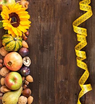 Fruits, légumes et fleurs d'automne avec du ruban à mesurer sur la vue de dessus de table en bois avec espace de copie