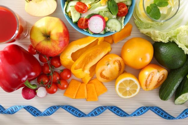 Fruits et légumes frais avec ruban à mesurer sur table en bois, vue du dessus