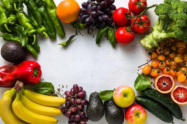 Fruits et légumes frais sur une table de cuisine blanche.