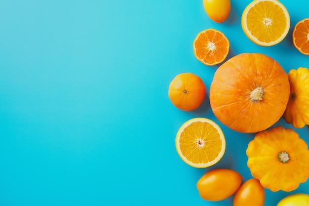 Fruits et légumes jaunes et oranges sur fond bleu automne concept copy space