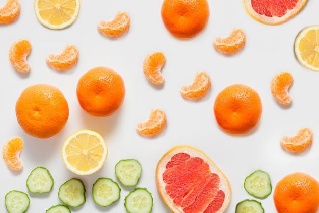 Fruits et légumes sur un mur blanc, y compris le citron et les mandarines d'agrumes, le pamplemousse et le concombre frais en tranches. vitamines concept, aliments sains, murs pour les épiceries.
