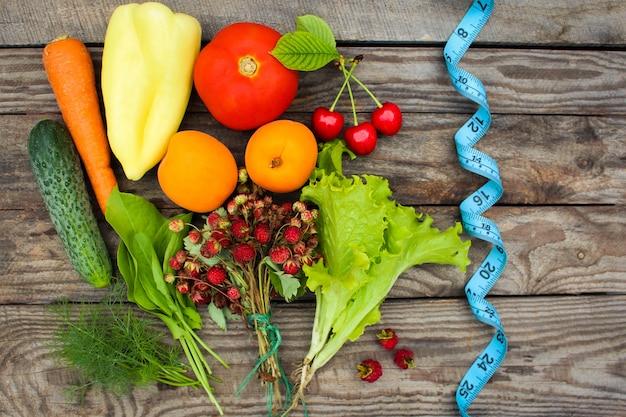 Fruits, légumes et ruban de mesure dans l'alimentation sur bois