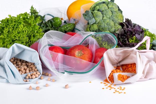 Fruits et légumes de saison sur blanc. aliments frais biologiques crus du marché. shopping zéro déchet. sacs d'épicerie réutilisables