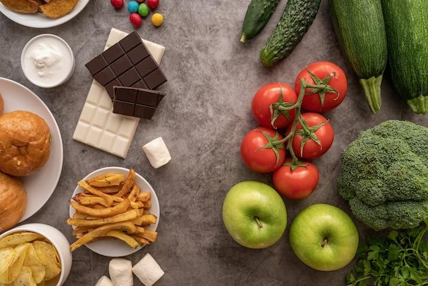 Fruits et légumes vs bonbons et pommes de terre frites vue de dessus à plat sur table sombre